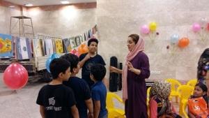 یک مربی در حال صحبت با بچهها درباره فعالیتهای مرتبط با کتاب / با من بخوان در بنیاد کودک - شهریور 94