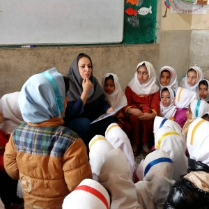 A trainer reads aloud with children - Read with Me in Zabol - Jan 2016
