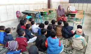 A tutor reads aloud with children - Read with Me in Zahedan - Jan 2016