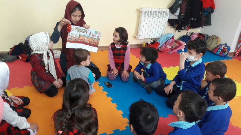 A tutor reads aloud with children - Read with Me in MahmoodAbad