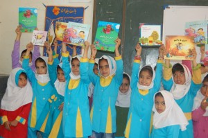Children in a Book Reading Session - Read with Me in Sistan and Balouchestan - March 2016 RWM cloth pocket library is seen on the wall