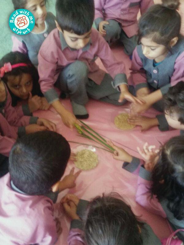 پیش از بلندخوانی بذر گندم و جو و خوشهای از گندم را به کودکان نشان دادم.