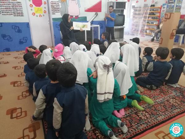 بلندخوانی کتاب توسط یکی از مروجان کتابخانه سیار قروه برای کودکان مهدکودک باران