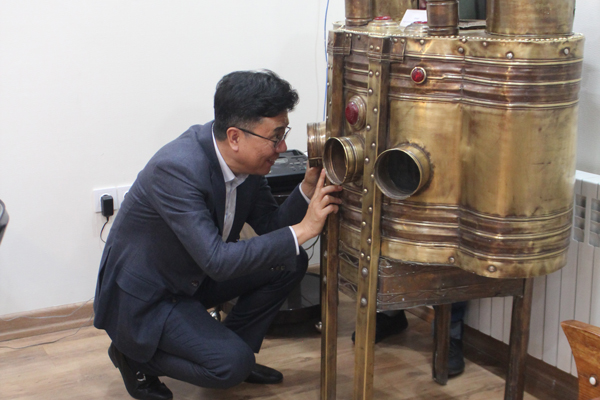 IBBY president looking through a Kinetoscope